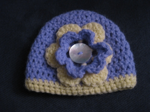 Sweet, little hat for that sweet little baby girl in your life. Pale purple and pale yellow with a pearl colored button in the middle. $12.